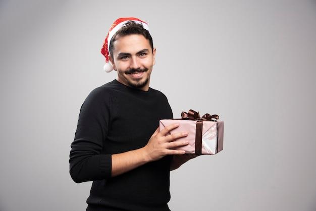 Um homem sorridente com um chapéu de papai noel segurando um presente de ano novo.