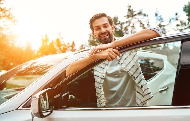 Um homem sorridente fica perto do carro no fundo da floresta. compra, aluguel de carro. descanse na natureza, fim de semana.