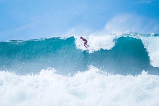 Um homem surfando em uma grande e extrema onda azul no oceano - horário de verão e aproveitando as férias