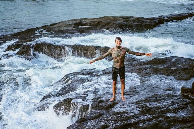 Um homem tatuado está à beira de um precipício. salpicos de ondas do mar.