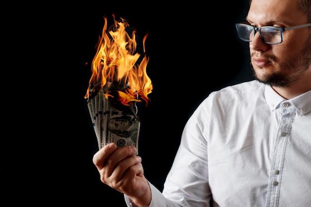 Um homem tem dinheiro em chamas na mão