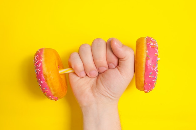 Um homem tem na mão um haltere de donuts com glacê rosa sobre fundo amarelo