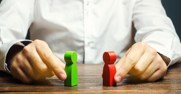 Um homem tem nas mãos a figura vermelha e verde