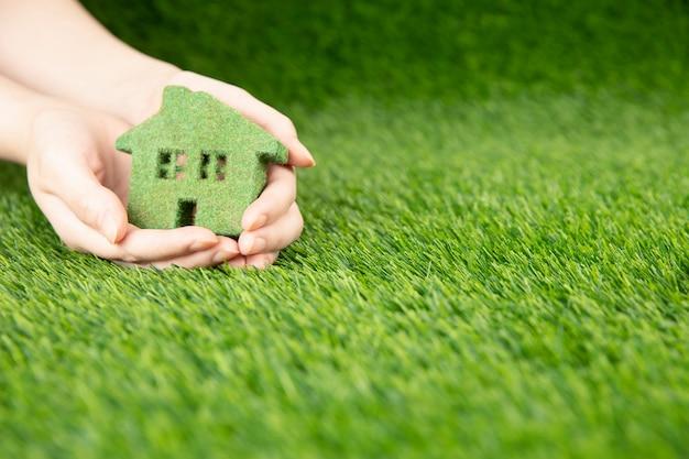 Um homem tem nas mãos uma pequena casa ecológica verde. uma cópia em miniatura da casa nas palmas das mãos em um fundo de grama.