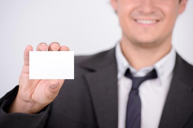 Um homem tem um cartão em branco nas mãos e sorrisos.