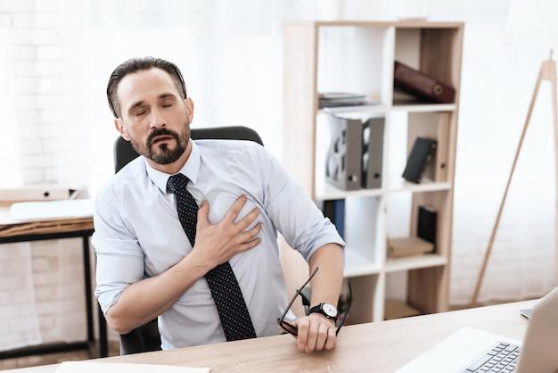 Um homem tem um coração ruim. ele segura as mãos no peito.