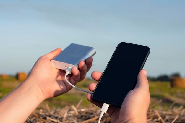 Um homem tem um smartphone e um carregador portátil nas mãos, no contexto da natureza e do céu.