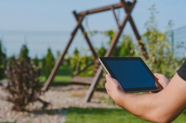Um homem tem um tablet nas mãos no contexto de um jardim com um balanço.