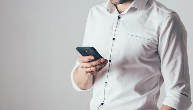 Um homem tem um telefone na mão. ele está vestido com uma camisa branca