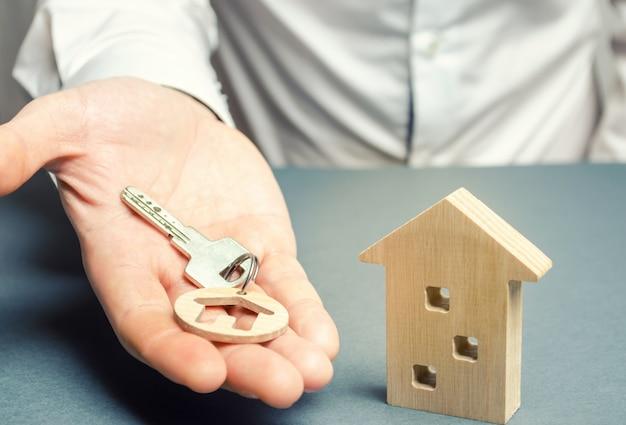 Um homem tem uma chave de bugiganga com uma casa