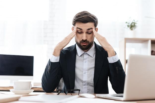 Um homem tem uma dor de cabeça ele mantém as mãos na cabeça