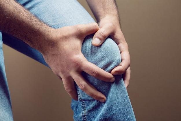 Um homem tem uma dor no joelho