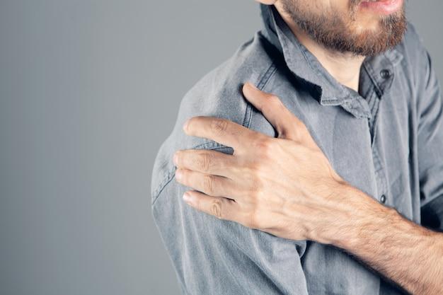 Um homem tem uma dor no ombro em um fundo cinza