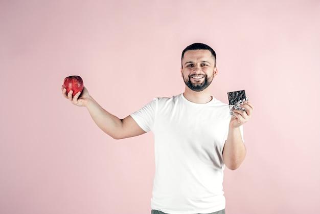 Um homem tem uma maçã e um chocolate nas mãos. alimentos saudáveis e não saudáveis.