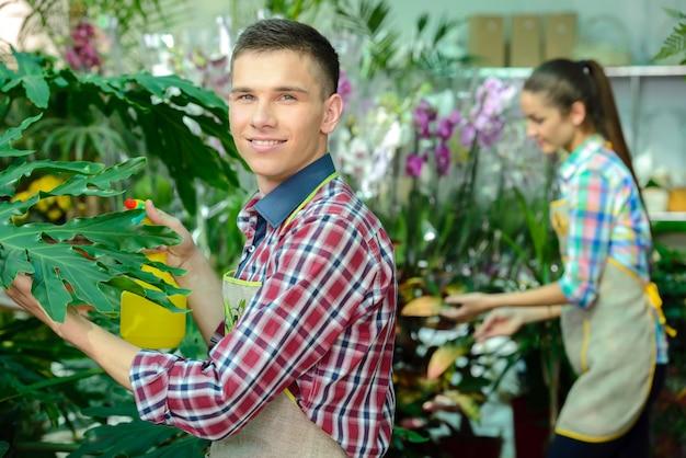 Um homem tem uma planta nas mãos e sorri.