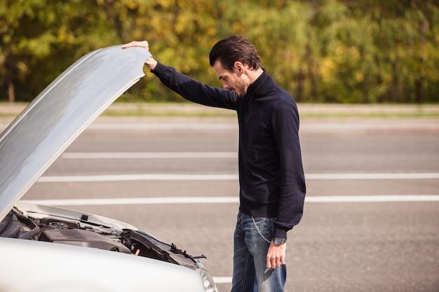 Um homem tenta reparar o carro na estrada