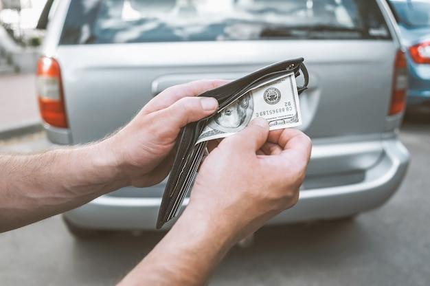 Um homem tira dinheiro de uma carteira de compra de um carro usado.