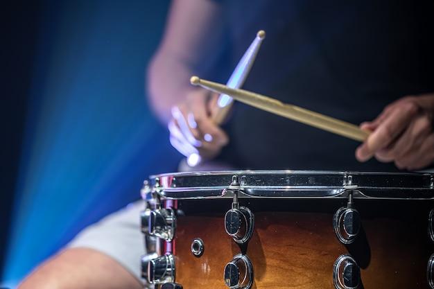 Um homem toca baquetas em um tambor, um baterista toca um instrumento de percussão, copie o espaço.