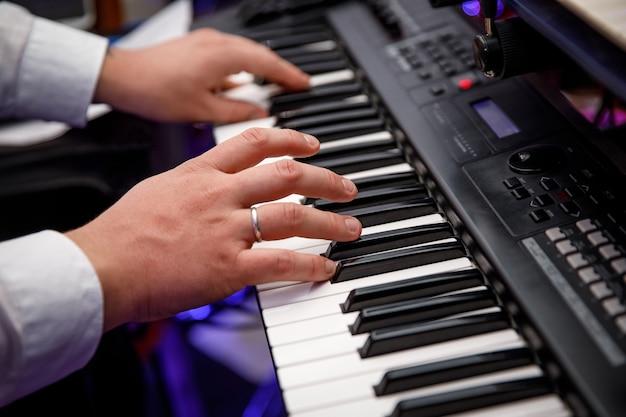 Um homem toca o sintetizador. dedos nas teclas.