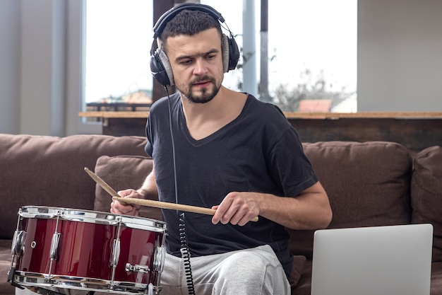 Um homem toca o tambor e olha para a tela do laptop. o conceito de aulas de música online, aulas de videoconferência.