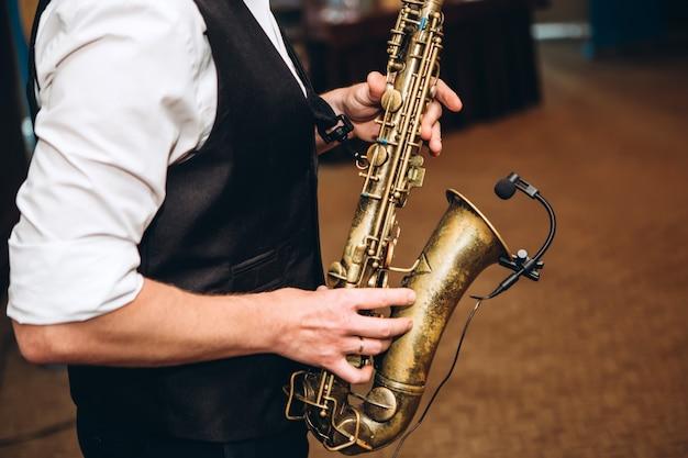 Um homem toca saxofone.