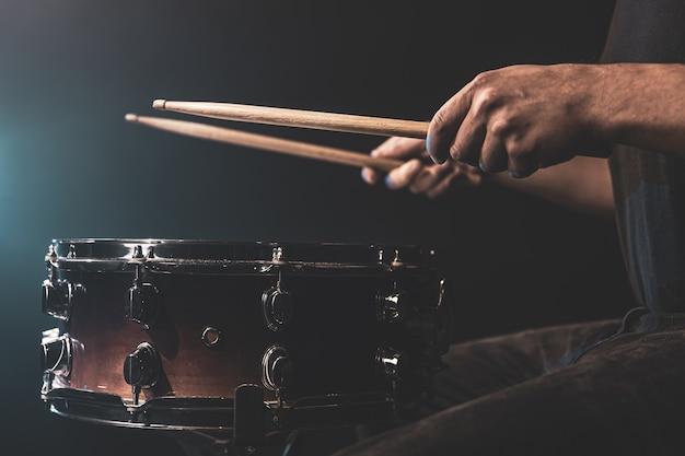 Um homem toca um tambor com baquetas, um baterista toca um instrumento de percussão, close-up.