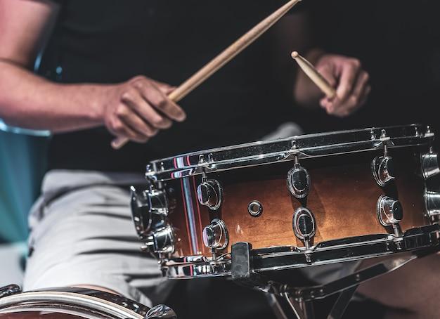 Um homem toca um tambor com baquetas, um baterista toca um instrumento de percussão.