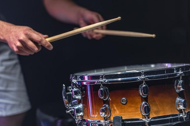Um homem toca uma caixa com baquetas, um baterista toca um instrumento de percussão, close up.