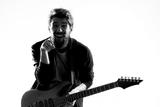 Um homem toca uma guitarra elétrica, foto em preto e branco