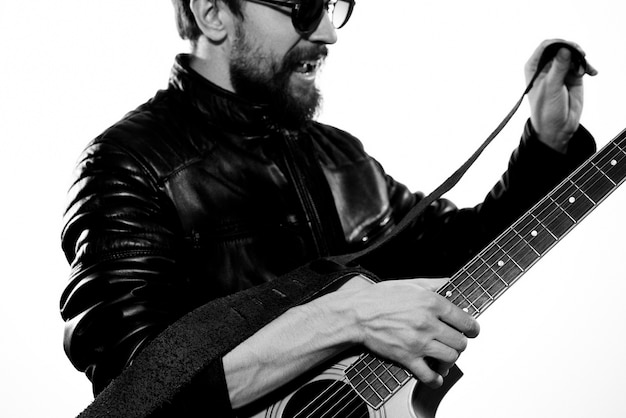Um homem toca violão com uma jaqueta de couro preta e óculos de sol