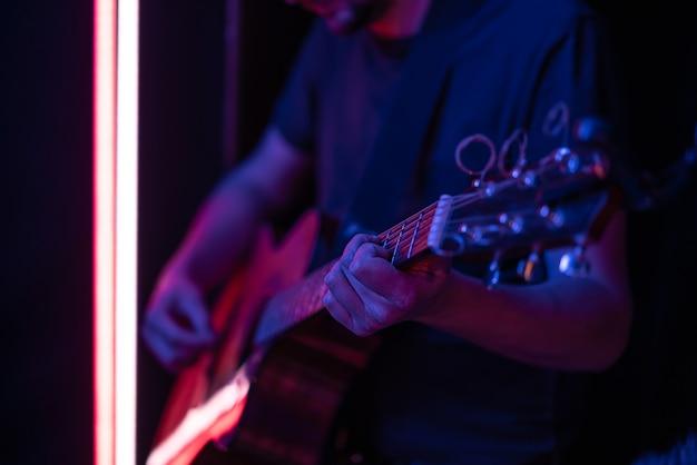 Um homem toca violão em um quarto escuro. performance ao vivo, concerto acústico.