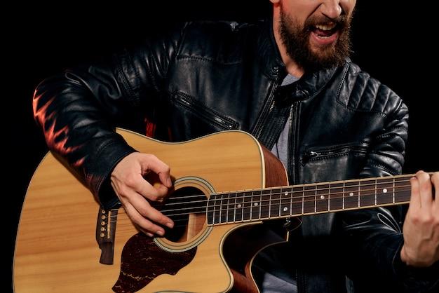 Um homem toca violão, um astro do rock, um músico estiloso com um violão