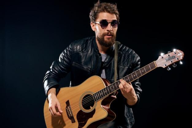 Um homem toca violão, uma estrela do rock, um músico estiloso com um violão