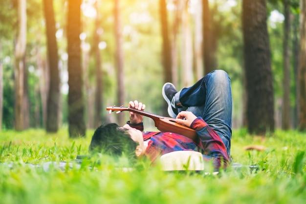 Um homem tocando cavaquinho deitado em um quintal verde