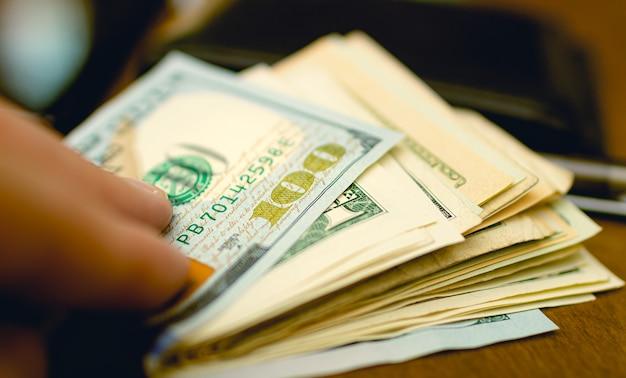 Um homem tocando um maço de notas de dólar americano que está sobre a mesa de madeira