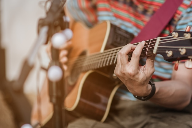 Um homem tocando violão no palco de um festival de música. concerto, mini concerto e festivais de música.
