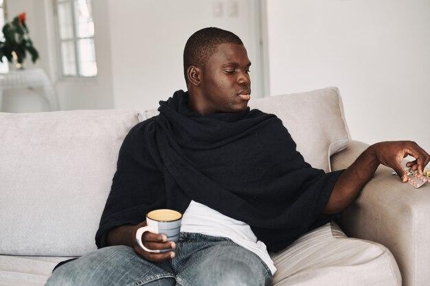 Um homem toma um comprimido e segura uma xícara na mão sentado no sofá problemas de saúde