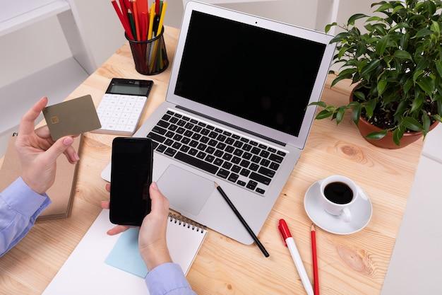 Um homem trabalha com laptop, calculadora, canetas, lápis, cartão, telefone e uma planta em sua área de trabalho no escritório