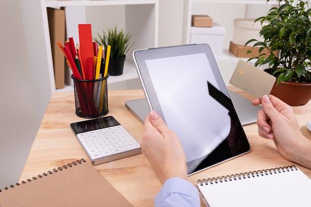 Um homem trabalha com um tablet e faz anotações em sua área de trabalho com calculadora, canetas, lápis, cartão, telefone e uma planta no escritório