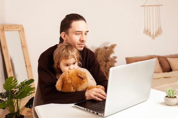 Um homem trabalha em casa em um laptop, a criança distrai do trabalho, sente falta do pai e da filha