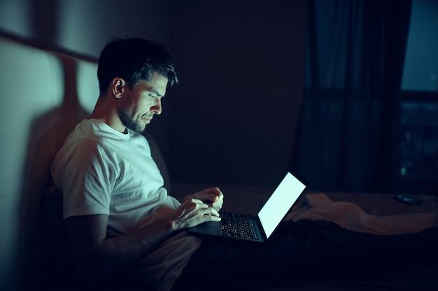 Um homem trabalha em um laptop na cama, uma amada dorme, trabalho noturno, traição