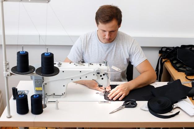 Um homem trabalha em uma máquina de costura na produção de costura. sem gênero