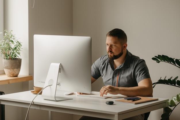 Um homem trabalha remotamente em um computador desktop. um cara com barba está digitando durante o relato de um colega em uma videoconferência em casa. um professor está se preparando para uma palestra online.