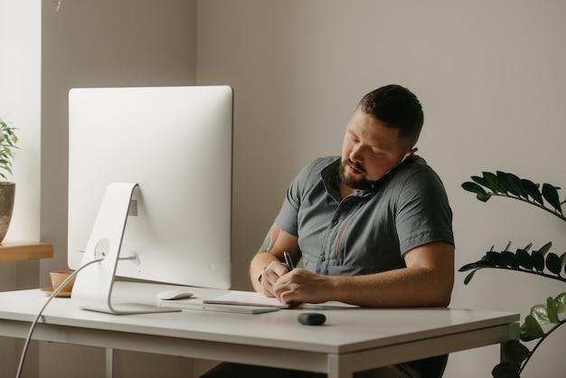 Um homem trabalha remotamente em um computador desktop. um cara com barba está fazendo anotações durante uma ligação telefônica para sua casa. um professor está se preparando para uma palestra online.