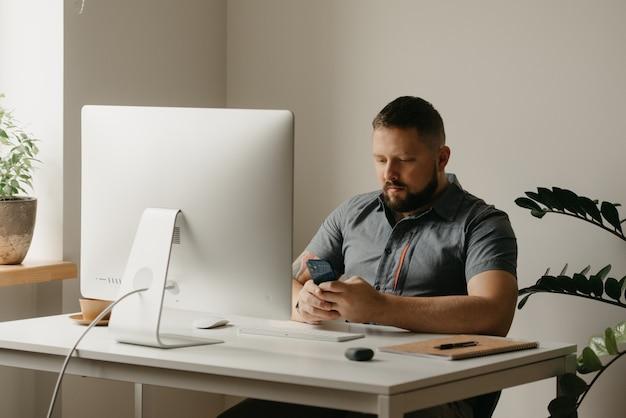 Um homem trabalha remotamente em um computador desktop. um cara com barba está navegando nas redes sociais durante uma reportagem de um colega em uma videoconferência em casa. um professor está se preparando para uma palestra online.