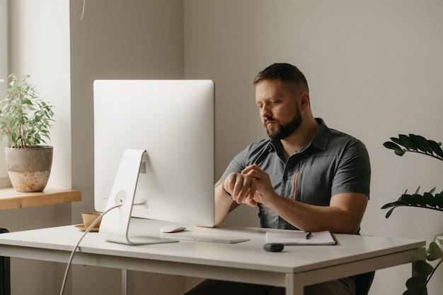 Um homem trabalha remotamente em um computador desktop. um cara com barba está rolando seu smartwatch durante uma videoconferência em casa. um professor está se preparando para uma palestra online.