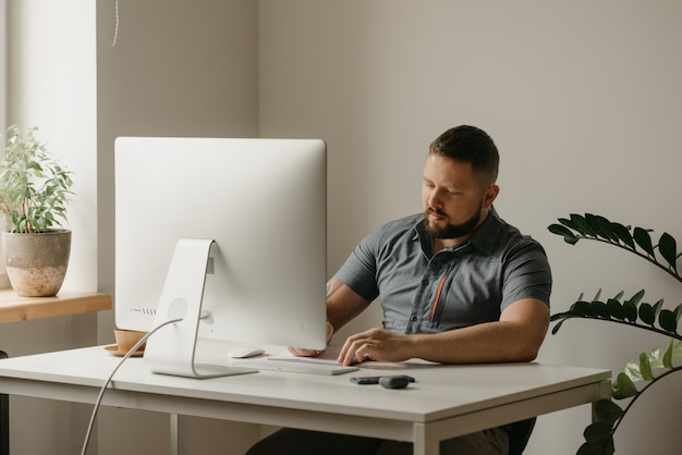 Um homem trabalha remotamente em um computador desktop. um cara com barba está tomando notas de um discurso do leitor durante uma videoconferência em casa. um professor está se preparando para uma palestra online.