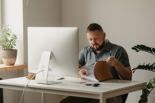 Um homem trabalha remotamente em um computador desktop. um cara de barba busca informações no notebook durante uma videoconferência em casa. um professor está se preparando para uma palestra online.