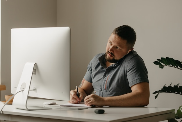 Um homem trabalha remotamente em um computador desktop. um cara de barba está fazendo anotações durante uma ligação telefônica e olhando para a tela do computador em casa. um professor está se preparando para uma palestra online.