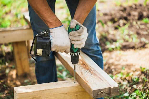 Um homem trabalha um prego, parafuso, chave de fenda, trabalha com as mãos, construção, tábuas, casa, verão, serra,